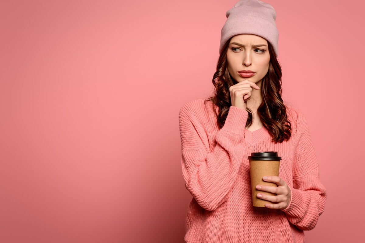 A young woman holding a compostable coffee cup.